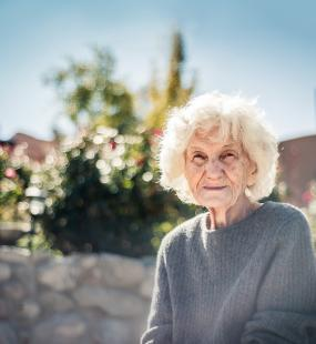 An older lady sits in the sunshine in the garden of a care home