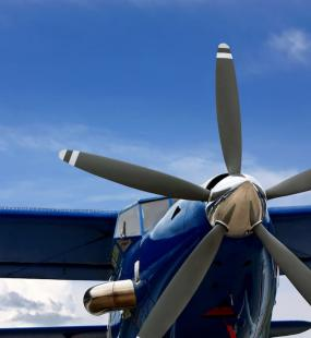 A blue propeller plane sits on a runway in front of a bright blue sky
