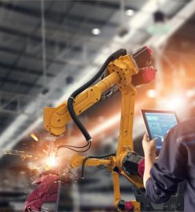 An engineer using a tablet computer checks the progress of automated robotic welding arms in a factory