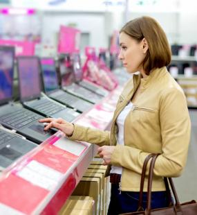A lady in a tan leather jacket tries out a new laptop in a technology store
