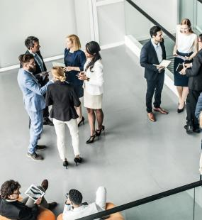 Young professionals stand talking in small groups in the foyer of an office building