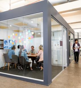 A group of business people sit at a board meeting in a glass-walled room
