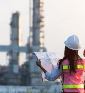 A female engineer holds up blueprints as she surveys a power station from a distance