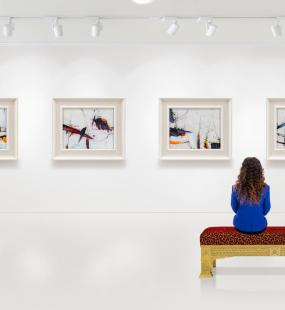 A young woman sits on a bench in a museum admiring the modern art on the wall in front of her