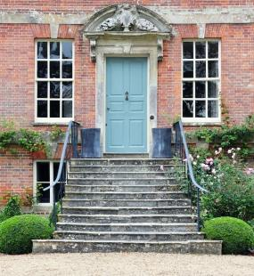 The front of a red brick country house, with large windows and a pale blue door at the top of a set of stone steps leading into a manicured garden