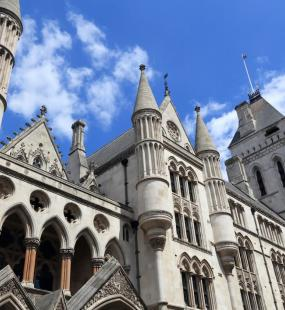 A view looking up at the Royal Courts of Justice against a bright blue sky