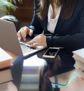 A female conveyancer sits at her desk using her laptop