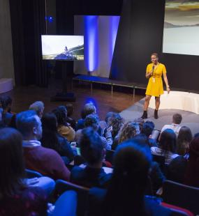A woman stands on stage giving a talk to an audience