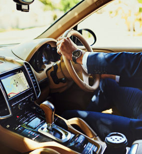 A handsome man in a tailored suit sits in an expensive car with his hands on the steering wheel