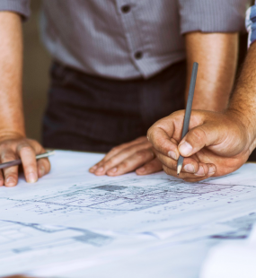 Two planning consultants lean over blueprints laid out on a desk