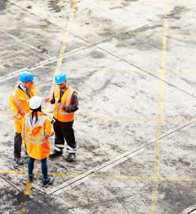 Three construction workers in hard hats and high vis jackets stand talking on a building site