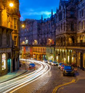 Edinburgh's Victoria Street at night, with brightly-painted shops lit up