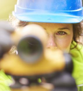 A female surveyor looks through a theodolite into the camera