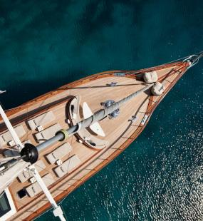 A view from the top of a mast looking down on a luxury yacht sailing in clear waters