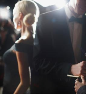 A man in a tuxedo signs an autograph book while a blonde woman in a ballgown is photographed by paparazzi behind him