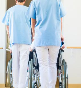 Two care workers in nurse scrubs push two wheelchairs through the corridor of a care home