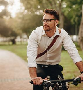 a man cycling to work through a park - flexible benefits covid-19 Howden