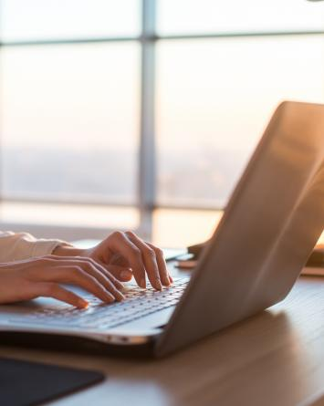A businesswoman types on a laptop as the sun sets through the large windows behind her