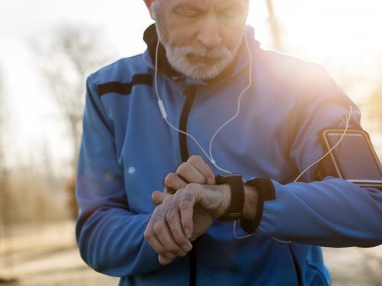 An older man checks his activity monitor while out running through sunny woods