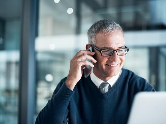 A smiling business man talks on the phone in an open plan office
