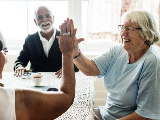 A group of smiling older people sit around a table, as two of them high five