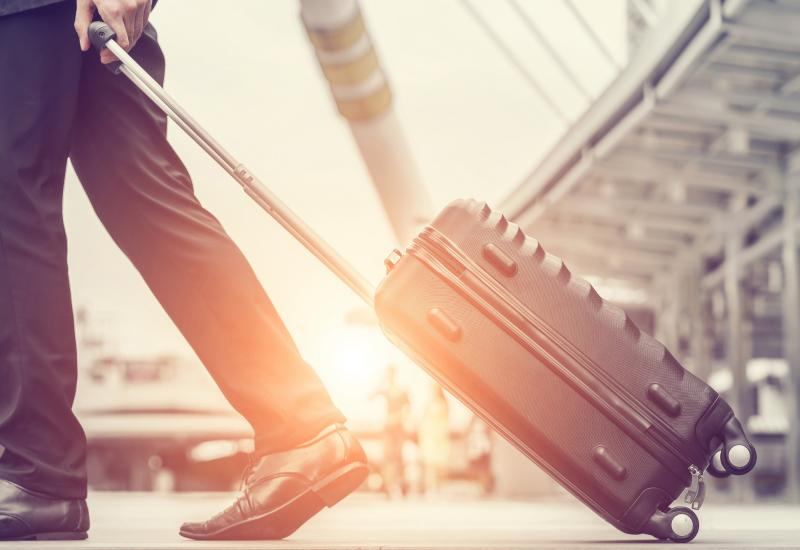 pulling suitcase at airport - expats employee benefits Howden