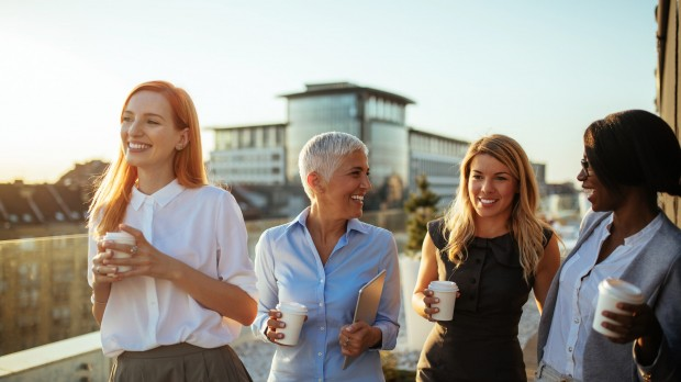 four female collegues drinking coffee and chatting laughing
