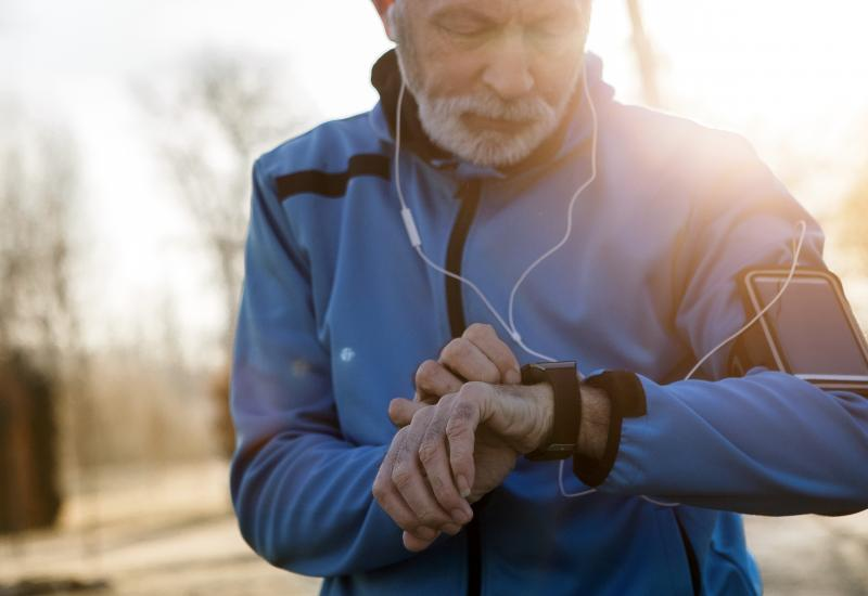 male jogger looking at watch wearing headphones outdoors