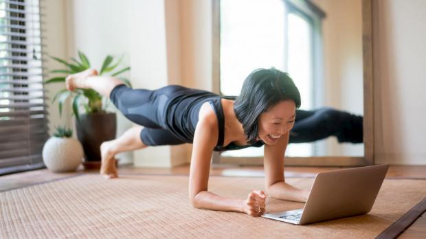 Woman doing yoga and looking at a laptop