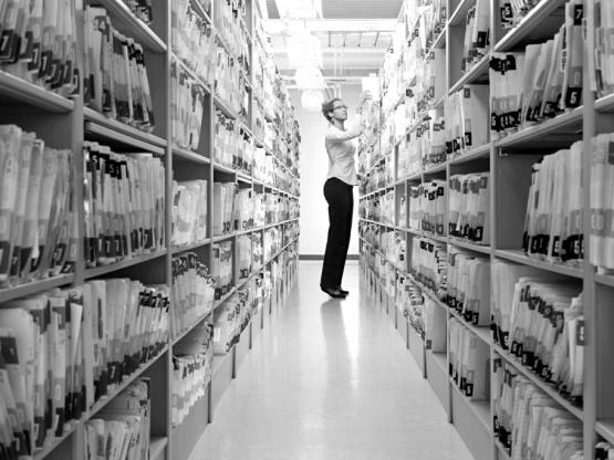Woman looking through shelves of paperwork records