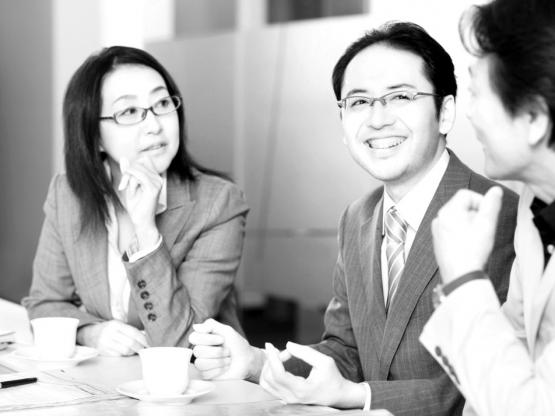 1 Asian woman 2 Asian men discussing business