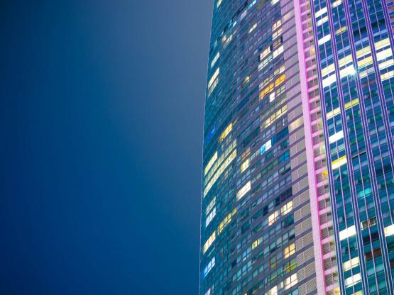 A modern tower block lit up at night