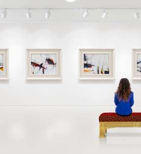 A young woman sits in an art gallery viewing four paintings on the wall