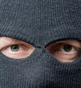 A man in a balaclava looks directly into the camera