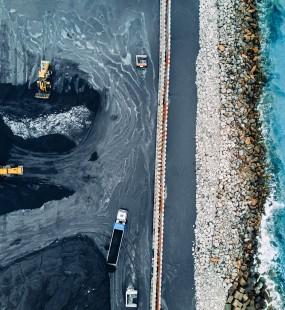 An aerial view of trucks moving coal by the coast