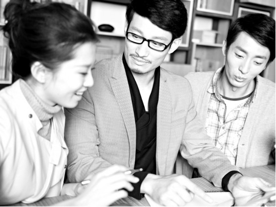 3 young Asian business people working in an office