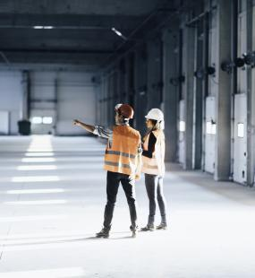 Two engineers view a large building in mid-construction