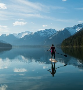 A woman paddle boards on a calm lake surrounded by mountains