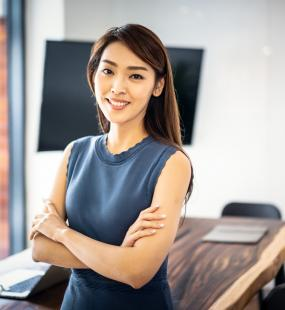 A confident business woman smiles with her arms folded