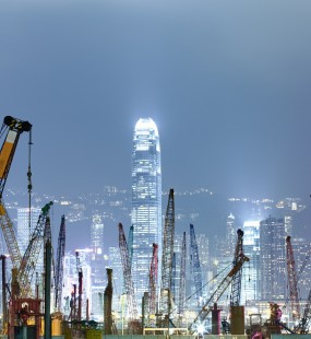 A nighttime view of the Hong Kong skyline with dozens of construction cranes in the foreground and illuminated skyscrapers behind