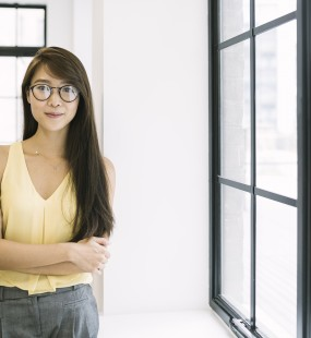 A young professional stands in an open plan office