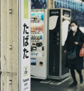 Two young people walk through Tabata Station in Tokyo, wearing face masks