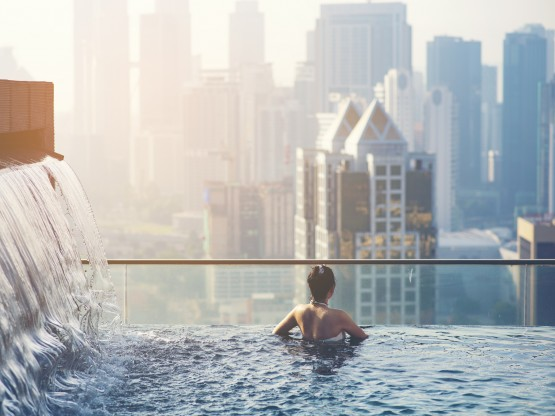 A traveler enjoys the view over the city from a rooftop pool with waterfall