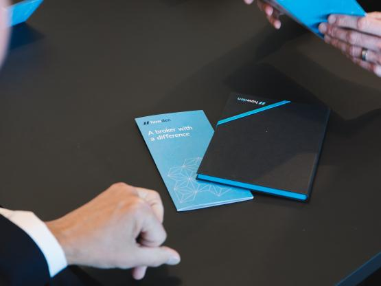 A Howden broker sits with a client, with a Howden notebook and brochure on the table between them