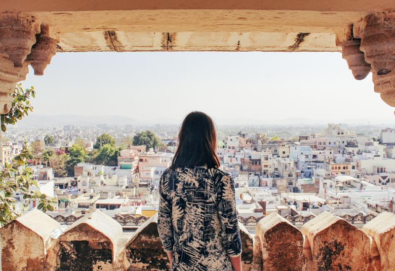A woman looks out at the view of Udaipur, Rajasthan