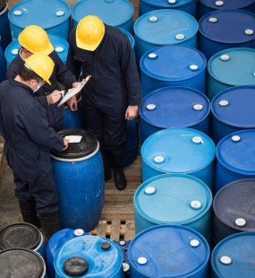 Two men inspecting a large amount of blue barrels
