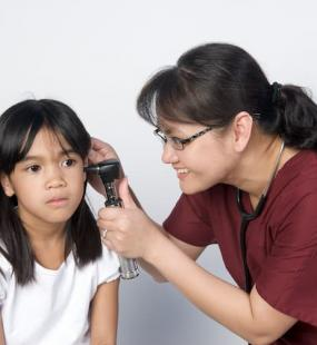 Doctor taking temperature in young girl's ear