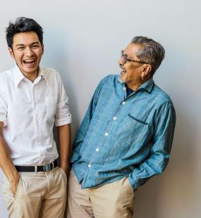 Father and son sharing a joke and laughing - Universal Life Insurance Howden Malaysia