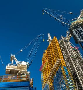high rise buildings being constructed with cranes - construction industry insurance - Howden Belgium