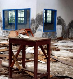 A white landline phone sits on a table in a ruined building, surrounded by rubble